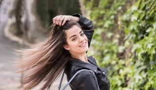 Modelo con una chaqueta negra luciendo su largo cabello lacio sobre sus hombros.