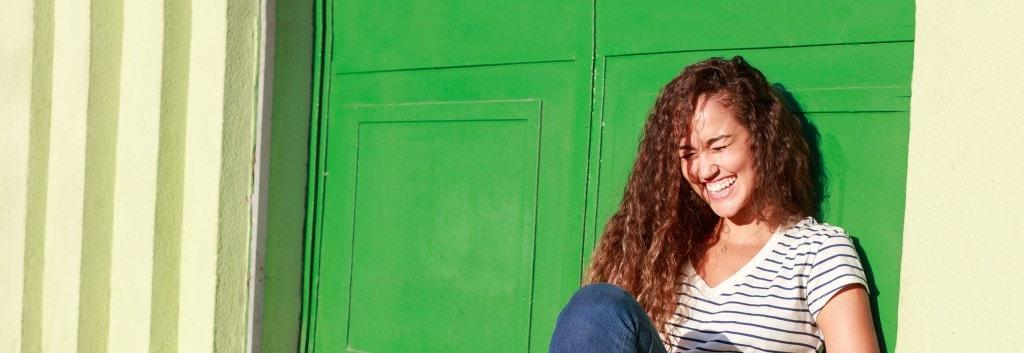 Mujer con pelo saludable con rizos, riendo y divirtiéndose sentada en el suelo.