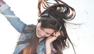 Una mujer con cabello brillante bailando con audífonos para ilustrar la página de shampoo Sedal.