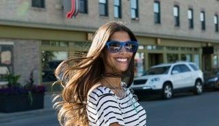 Mujer feliz con pelo largo sedoso sonriendo mientras cruza la calle.