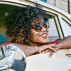 Mujer con pelo rizado sonriendo, con gafas de sol, asomanda por la ventanilla del carro.
